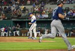 Texas Rangers starting pitcher Spencer Howard walks back to the mound after giving up a three run home run to Seattle Mariners' Mitch Haniger, right, during the second inning of a baseball game Thursday, Aug. 19, 2021, in Arlington, Texas. (AP Photo/Jeffrey McWhorter)