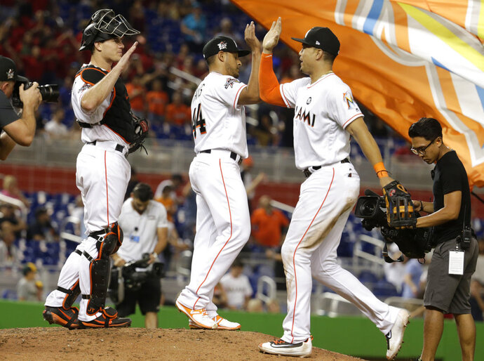FILE - In this May 26, 2017, file photo, Miami Marlins catcher J.T. Realmuto, left, relief pitcher AJ Ramos, left, and right fielder Giancarlo Stanton, right, celebrate after defeating the Los Angeles Angels 8-5 during an interleague baseball game in Miami. Giancarlo Stanton and AJ Ramos, former teammates with the Miami Marlins and still close friends, are looking into living together this season now that both play in New York. It would seem to be a convenient arrangement, with at least one player on the road most of the time anyway _ except when Stanton and the Yankees face Ramos and the Mets in the Subway Series. (AP Photo/Lynne Sladky, File)