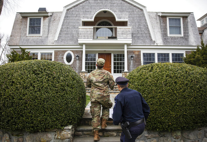Rhode Island Air National Guard Tsgt. William Randall, left, and Westerly police officer Howard Mills approach a home while looking for New York license plates in driveways to inform them of self quarantine orders, Saturday, March 28, 2020, in Westerly, R.I. States are pulling back the welcome mat for travelers from the New York area, which is the epicenter of the country's coronavirus outbreak, and some say at least one state's measures are unconstitutional. Gov. Gina Raimondo ratcheted up the measures announcing she ordered the state National Guard to go door-to-door in coastal communities starting this weekend to find out whether any of the home's residents have recently arrived from New York and inform them of the quarantine order. (AP Photo/David Goldman)