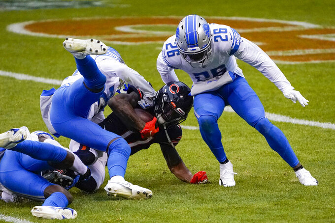 Chicago Bears wide receiver Anthony Miller (17) is tackled after picking up a first down by Detroit Lions strong safety Duron Harmon (26) and cornerback Amani Oruwariye (24) in the first half of an NFL football game in Chicago, Sunday, Dec. 6, 2020. (AP Photo/Charles Rex Arbogast)