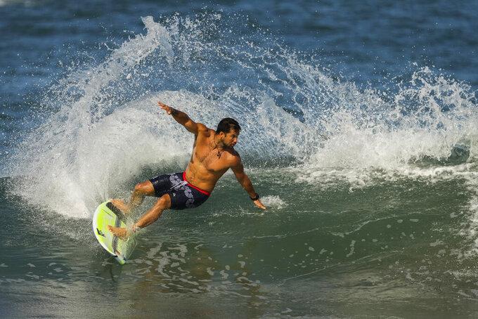 France's Michel Bourez rides a wave during a training session at the 2020 Summer Olympics, Friday, July 23, 2021, at Tsurigasaki beach in Ichinomiya, Japan. (AP Photo/Francisco Seco)