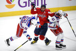 New York Rangers defenseman Ryan Lindgren (55) loses his balance after he collided with Washington Capitals left wing Alex Ovechkin, center, during the second period of an NHL hockey game Friday, March 19, 2021, in Washington. At right is Rangers center Colin Blackwell (43). (AP Photo/Nick Wass)