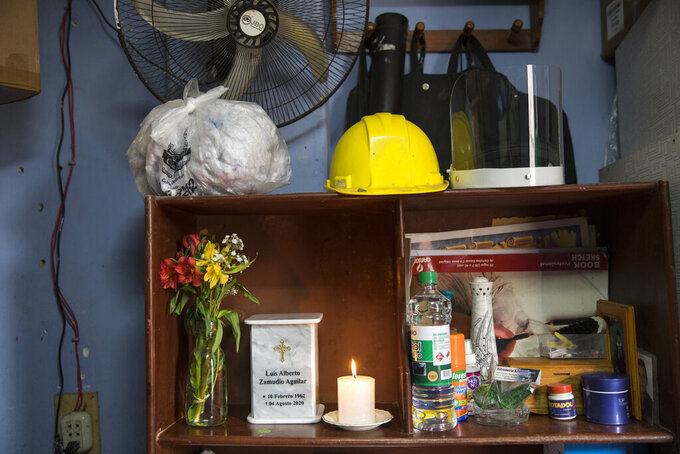A marble urn that contains the cremated remains of security guard Luis Zamudio, who died from symptoms related to COVID-19 at the age of 58, sits on a shelf along with his helmet and his face shield at his home in Lima, Peru, Friday, Aug. 7, 2020. (AP Photo/Rodrigo Abd)