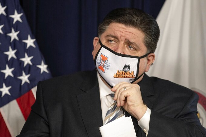 """FILE - In this March 18, 2021 file photo, Gov. J.B. Pritzker adjusts his mask during a press conference at the James R. Thompson Center in Chicago.   A recent spike in coronavirus cases in some states has led one of the nation's top health experts to suggest that governors could """"close things down"""" like they did during previous surges. But that doesn't appear likely to happen — not even in states led by Democratic governors who favored greater restrictions in the past.  (Pat Nabong/Chicago Sun-Times via AP)"""