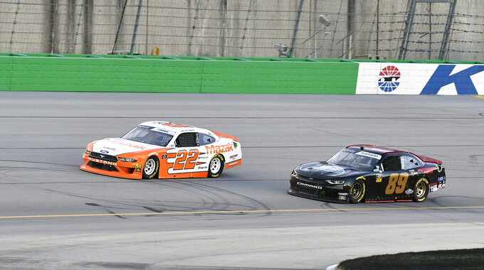 Austin Cindric (22) tries to fight off the challenge from Morgan Shepherd (89) during the NASCAR Xfinity Series auto race at Kentucky Speedway in Sparta, Ky., Friday, July 12, 2019. (AP Photo/Timothy D. Easley)