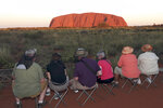 FILE - In this April 22, 2014, file photo, people sit on camp chairs at a popular viewing point to watch the sunset on Uluru, Australia. A climbing ban from late Friday, Oct. 25, 2019 on the sandstone monolith called Uluru that dominates Australia's arid center marks indigenous Australians finding a new voice in national decision-making. The rock has long been celebrated as a prized peak to conquer and a sacred site to be revered, but with the ban, the pendulum is swinging decisively toward the rock's cultural significance to its traditional owners. (AP Photo/Rob Griffith, File)