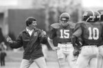 FILE - University of Alabama head coach Ray Perkins explains techniques to his quarterbacks in Tuscaloosa, Ala., in this March 23, 1983, file photo. Players shown are Ernest Carroll (15) and Walter Lewis (10).  Perkins, who replaced Hall of Famer Bear Bryant as Alabama's football coach and started the transition with the New York Giants that led to two Super Bowl titles, died Wednesday morning, Dec. 9, 2020, in Tuscaloosa. He was 79. The school announced his passing on Wednesday, and daughter Rachael Perkins posted news of his death on her Facebook page. (AP Photo/File)