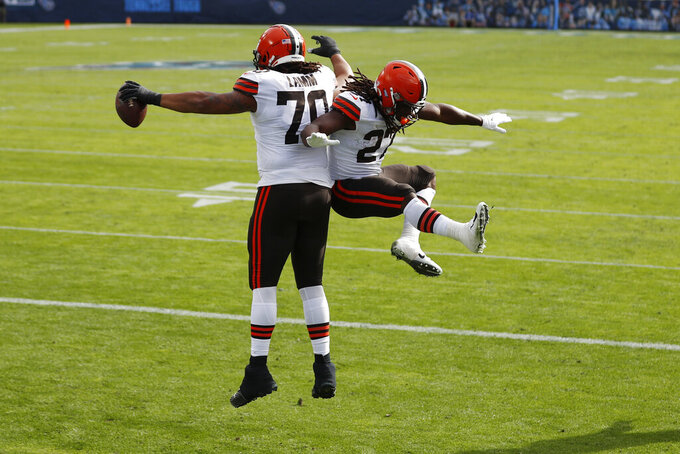 Cleveland Browns offensive tackle Kendall Lamm (70) celebrates with running back Kareem Hunt (27) after Lamm caught a touchdown pass against the Tennessee Titans in the first half of an NFL football game Sunday, Dec. 6, 2020, in Nashville, Tenn. (AP Photo/Wade Payne)