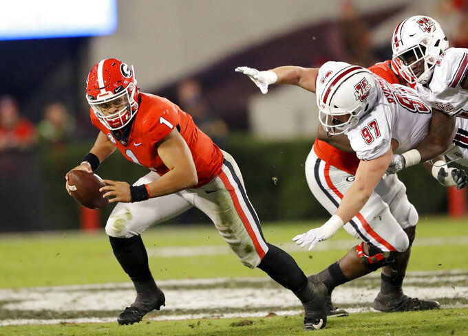 Georgia quarterback Justin Fields (1) runs away from Massachusetts defensive lineman Jake Byczko (97) during the second half of an NCAA college football game Saturday, Nov. 17, 2018, in Athens, Ga. (AP Photo/John Bazemore)