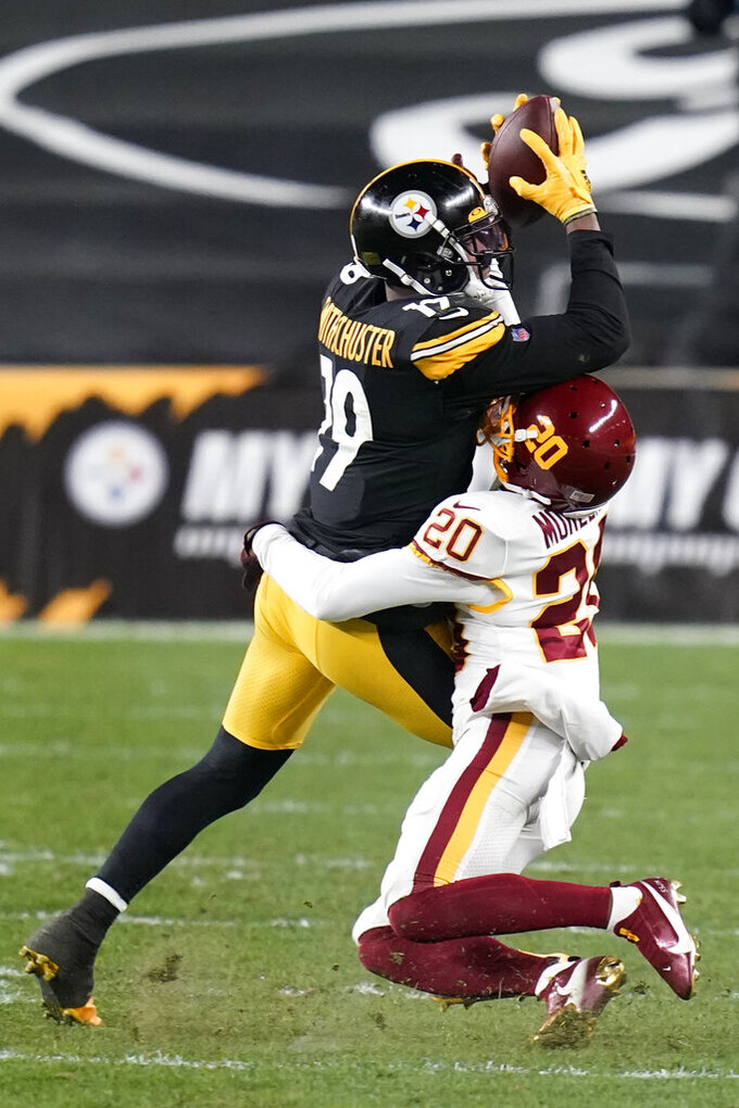 Pittsburgh Steelers wide receiver JuJu Smith-Schuster (19) comes down with the ball with Washington Football Team cornerback Jimmy Moreland (20) defending during the second half of an NFL football game, Monday, Dec. 7, 2020, in Pittsburgh. (AP Photo/Keith Srakocic)