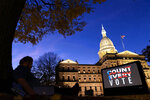 "FILE - In this Nov. 6, 2020, file photo, the phrase ""Count Every Vote"" is displayed on a large screen, organized by an advocacy group in front of thesState Capitol while election results in several states had yet to be finalized, in Lansing, Mich. (AP Photo/David Goldman, File)"