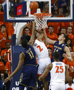 Virginia guard Braxton Key (2) puts up a shot as he is blocked out by Notre Dame forward Juwan Durham (11) and Nate Laszewski (14) during the first half of an NCAA college basketball game in Charlottesville, Va., Saturday, Feb. 16, 2019. (AP Photo/Steve Helber)