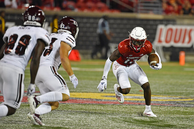 Louisville defensive back Kei'Trel Clark (13) attempts to break away from the pursuit of Eastern Kentucky linebacker Khalil Arnold (83) and Jaden Smith (88) during the second half of an NCAA college football game in Louisville, Ky., Saturday, Sept. 11, 2021. (AP Photo/Timothy D. Easley)