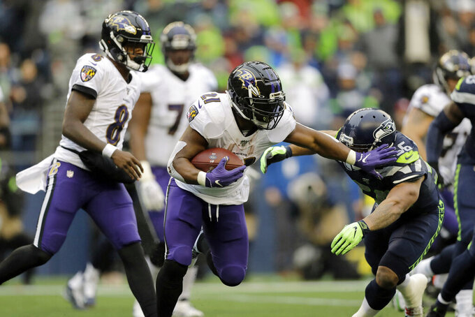 Baltimore Ravens running back Mark Ingram (21) fends off Seattle Seahawks linebacker Mychal Kendricks, right, as Ravens quarterback Lamar Jackson (8) looks on during the second half of an NFL football game, Sunday, Oct. 20, 2019, in Seattle. (AP Photo/John Froschauer)