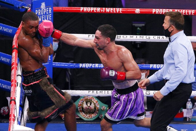 Errol Spence Jr., left, covers up as Danny Garcia, right, delivers a punch during the WBC-IBF welterweight boxing bout in Arlington, Texas, Saturday, Dec. 5, 2020. (AP Photo/Brandon Wade)