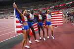 The team from the United States celebrates after winning the gold medal in the women's 4 x 400-meter relay at the 2020 Summer Olympics, Saturday, Aug. 7, 2021, in Tokyo. (AP Photo/David J. Phillip)