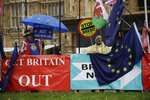 Anti-Brexit remain in the European Union supporter Steve Bray, left, protests next to banners placed by pro-Brexit leave the EU supporters backdropped by the Houses of Parliament in London, Thursday, Oct. 24, 2019. Britain's Prime Minister Boris Johnson won Parliament's backing for his exit deal on Wednesday, but then lost a key vote on its timing, effectively guaranteeing that Brexit won't happen on the scheduled date of Oct. 31. (AP Photo/Matt Dunham)