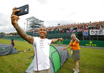 Mercedes' Lewis Hamilton takes a selfie during a preview day for the British Grand Prix at Silverstone racetrack, in Silverstone, England, Thursday July 11, 2019. The British Formula One Grand Prix will be held on Sunday. (Martin Rickett/PA via AP)