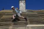 Timotei Pacurar repairs the roof of the dilapidated 16th-century Brukenthal Castle, during works done by volunteers supporting the Ambulance for Monuments project in Micasasa, Romania, Saturday, June 5, 2021. One of the young people directly involved in the efforts to save the endangered building from ruin is Micasasa's mayor, 30-year-old Timotei Pacurar. For him, saving the village's most significant and perhaps most neglected historic building holds a poignant significance. (AP Photo/Vadim Ghirda)