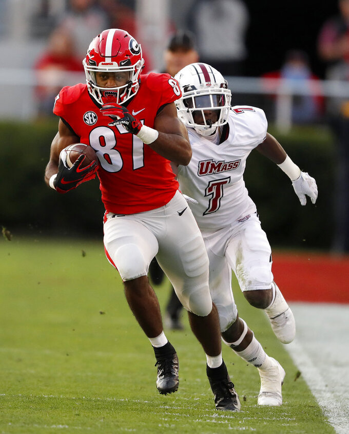 Georgia wide receiver Tyler Simmons (87) out runs Massachusetts Joseph Norwood as he runs for a touchdown after a catch during the first half of an NCAA college football game Saturday, Nov. 17, 2018, in Athens, Ga. (AP Photo/John Bazemore)