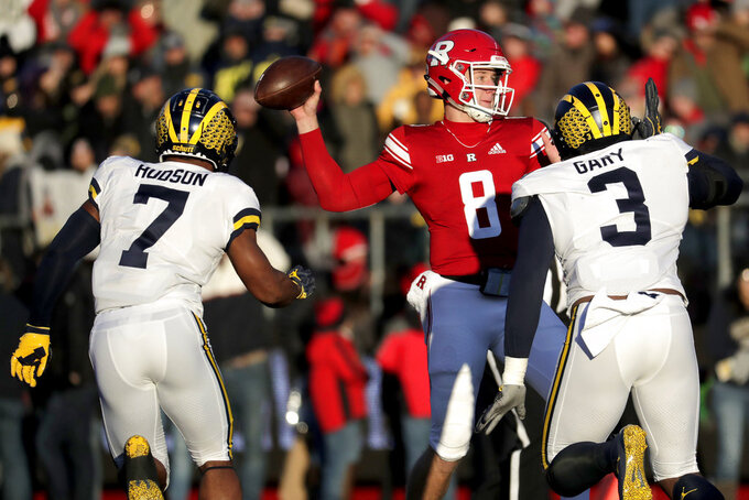 Rutgers quarterback Artur Sitkowski (8) looks to pass as Michigan linebacker Khaleke Hudson (7) and defensive lineman Rashan Gary (3) apply pressure during the first half of an NCAA college football game, Saturday, Nov. 10, 2018, in Piscataway, N.J. (AP Photo/Julio Cortez)