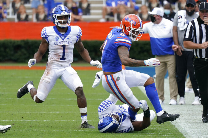 Florida wide receiver Trevon Grimes, right, is tackled by Kentucky defensive back Cedrick Dort Jr., bottom center, as defensive back Kelvin Joseph (1) comes in to help during the first half of an NCAA college football game, Saturday, Nov. 28, 2020, in Gainesville, Fla. (AP Photo/John Raoux)