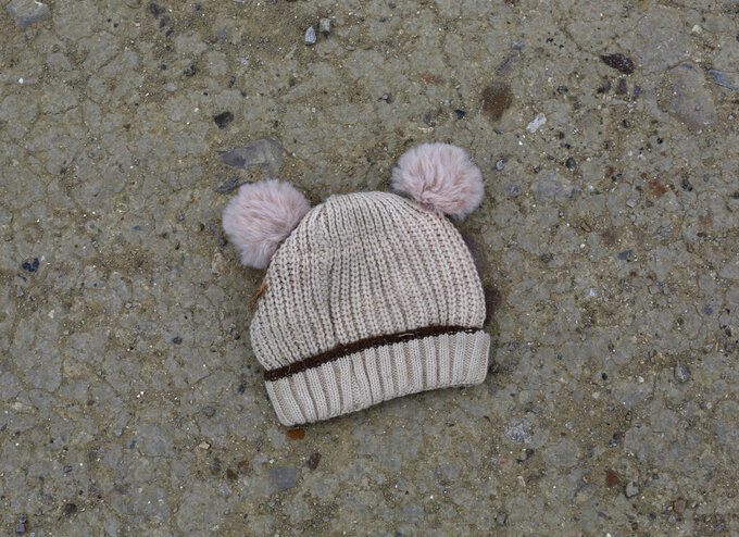 FILE - In this March 28, 2021, file photo, a child's knitted cap lies on the ground near the banks of the Rio Grande river in Roma, Texas. Confronted with a stream of unaccompanied children crossing the border from Mexico, the U.S. government has awarded shelter-construction and management contracts to private companies that critics say may not be equipped to adequately care for the minors. (AP Photo/Dario Lopez-Mills, File)