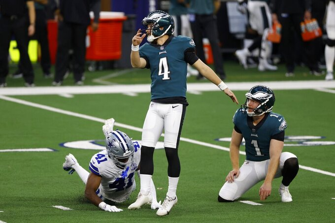 Philadelphia Eagles' Jake Elliott (4) and Cameron Johnston (1) watch their successful field goal under pressure from Dallas Cowboys cornerback Reggie Robinson II (41) in the first half of an NFL football game in Arlington, Texas, Sunday, Dec. 27. 2020. (AP Photo/Ron Jenkins)