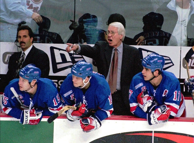 FILE - In this Dec. 4, 1999, file photo, New York Rangers coach John Muckler yells instructions to his players on the ice during the third period against the Buffalo Sabres at Marine Midland Arena in Buffalo, N.Y. Muckler, a former NHL coach and five-time Stanley Cup winner with the Edmonton Oilers has died. He was 86. (AP Photo/Don Heupel, File)