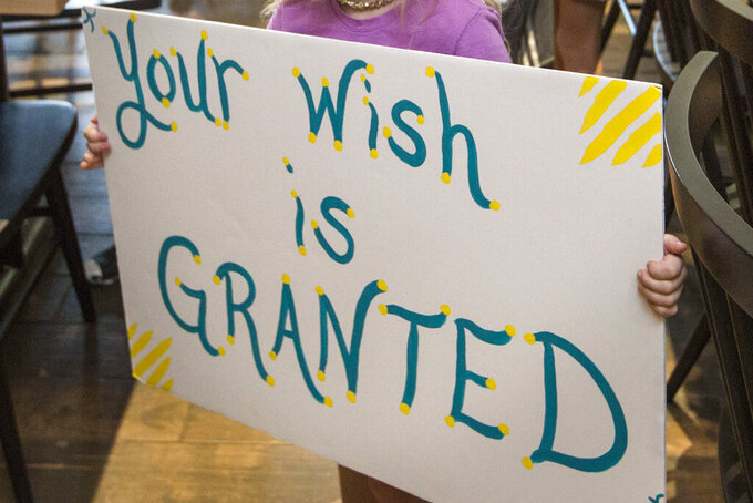 """FILE - In this Thursday, Aug. 22, 2019 photo, a girl holds a sign while waiting for her cousin to arrive for a surprise Make-A-Wish announcement in Rogers, Ark. In June 2021, the Make-a-Wish Foundation is disputing what it calls a """"misinformation"""" campaign about whether children who aren't vaccinated against COVID-19 will be eligible to have their wishes granted. (Ben Goff/The Northwest Arkansas Democrat-Gazette via AP)"""