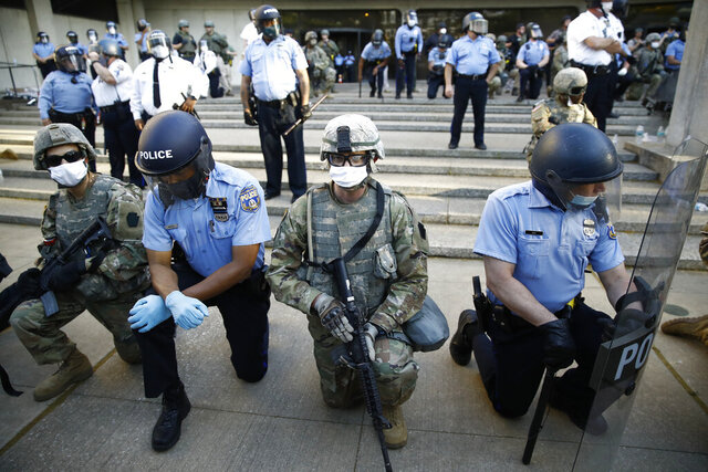 FILE - In this June 1, 2020, file photo, Philadelphia police and Pennsylvania National Guard take a knee at the suggestion of Philadelphia Police Deputy Commissioner Melvin Singleton, unseen, outside Philadelphia Police headquarters in Philadelphia, during a march calling for justice over the death of George Floyd. If the military has any role in next week's election, it most likely will involve National Guard members under state control — not troops on federal duty.  (AP Photo/Matt Rourke, File)