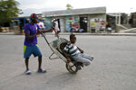 In this Dec. 3, 2019 photo, a young man pushes a wheelbarrow home as his little brother takes a ride on it, in the Cite Soleil slum of Port-au-Prince, Haiti. The two youths are going home after helping their mother by carrying items to sell in the market. In the last two years, Haiti's currency, the gourde, declined 60% against the dollar and inflation recently reached 20%. (AP Photo/Dieu Nalio Chery)