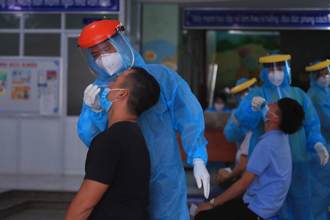 Medical workers take swab samples from people in Vung Tau city, Vietnam Saturday, Aug. 21, 2021. Vietnam's government said it is sending troops to Ho Chi Minh city to help deliver food and aid to households as it further tightens restrictions on people's movements amid a worsening surge of the coronavirus. (AP Photo/Hau Dinh)