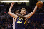 Indiana Pacers forward Domantas Sabonis (11) is fouled by Phoenix Suns center Deandre Ayton during the first half of an NBA basketball game, Wednesday, Jan. 22, 2020, in Phoenix. (AP Photo/Matt York)