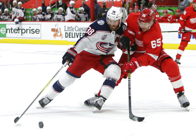 Columbus Blue Jackets center Boone Jenner (38) tries to hold off Detroit Red Wings defenseman Danny DeKeyser (65) during the third period of an NHL hockey game Tuesday, Jan. 19, 2021, in Detroit. (AP Photo/Duane Burleson)