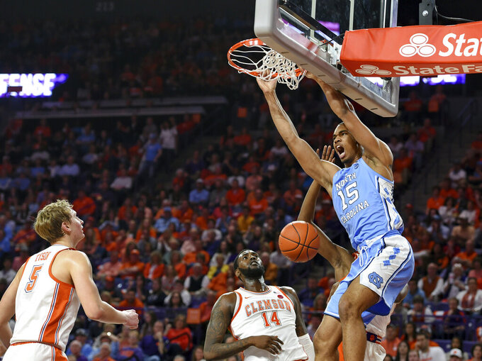 North Carolina's Garrison Brooks dunks while defended by Clemson's Elijah Thomas (14) and Hunter Tyson during the first half of an NCAA college basketball game Saturday, March 2, 2019, in Clemson, S.C. (AP Photo/Richard Shiro)