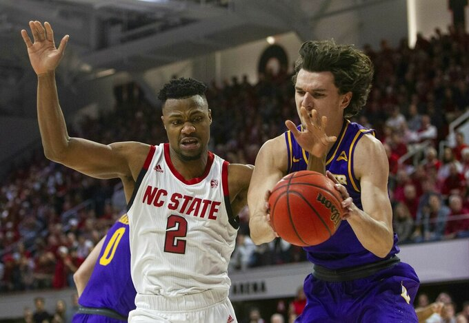 North Carolina State's Torin Dorn (2) tries to take the ball form Lipscomb's Eli Pepper during the first half of an NCAA college basketball game in the quarterfinals of the NIT on Wednesday, March 27, 2019, in Raleigh, N.C. (Travis Long/The News & Observer via AP)