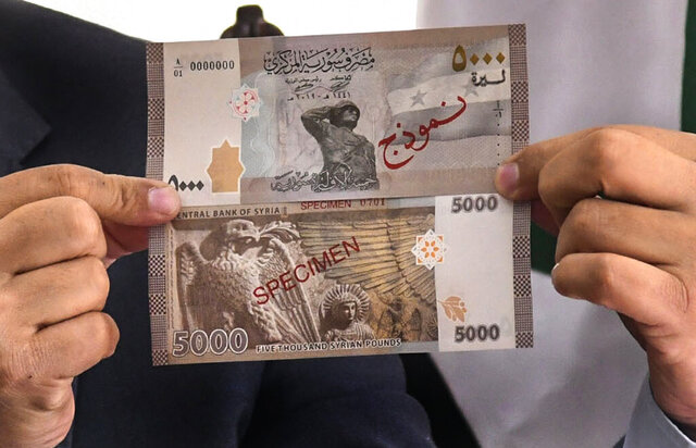 In this photo released by the Syrian official news agency SANA, Iyed Bilal, the director of the treasury department of the Syrian Central Bank, shows the new banknote of 5000 Syrian pounds during a press briefing, in Damascus, Syria, Sunday, Jan. 24, 2021. The new 5,000 Syrian Lira bank note goes into circulation Sunday, the largest denomination in the country reeling from 10 years of conflict and a crippling economic crisis. (SANA via AP)