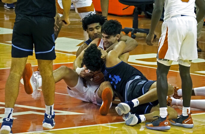 Texas forward Brock Cunningham, center, fights for a loose ball with Villanova forward Jeremiah Robinson-Earl, front, and Jermaine Samuels, back, during the second half of an NCAA college basketball game, Sunday, Dec. 6, 2020, in Austin, Texas. Villanova won 68-64. (AP Photo/Michael Thomas)