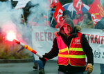 A trade union demonstrator holds a flare, during a protest in Bayonne, southwestern France, Thursday, Dec. 12, 2019. France's prime minister said Wednesday that the full retirement age will be increased for the country's youngest, but offered concessions in an ill-fated effort to calm a nationwide protest against pension reforms that critics say will erode the nation's way of life. (AP Photo/Bob Edme)