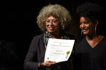 FILE- In this March 23, 2019 file photo, American political activist Angela Davis, left, receives the Honoris Causa from Noelia Ojeda, during an open air rally in front of the University of the Republic in Montevideo, Uruguay. Davis is among 10 people who will be inducted into the National Women's Hall of Fame during a ceremony on Saturday, Sept. 14, 2019. (AP Photo/Matilde Campodonico, File)