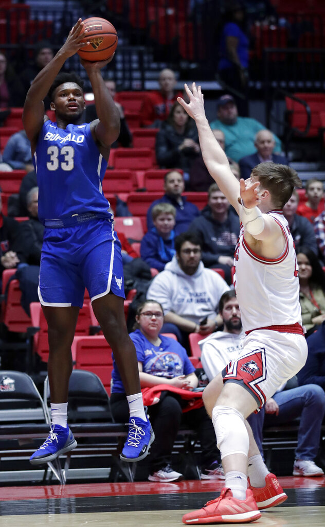 Buffalo forward Nick Perkins, left, shoots against Northern Illinois forward Noah McCarty during the first half of an NCAA college basketball game Tuesday, Jan. 22, 2019, in DeKalb, Ill. (AP Photo/Nam Y. Huh)