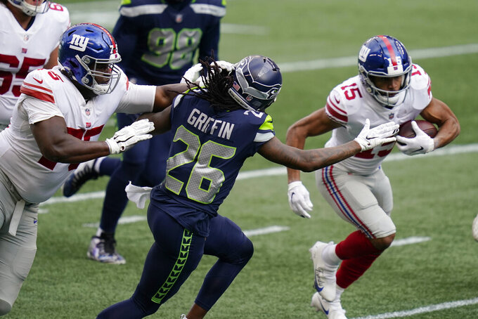 Seattle Seahawks cornerback Shaquill Griffin (26) moves to tackle New York Giants wide receiver Golden Tate (15) as New York Giants offensive tackle Cameron Fleming, left, moves in, during the first half of an NFL football game, Sunday, Dec. 6, 2020, in Seattle. (AP Photo/Elaine Thompson)