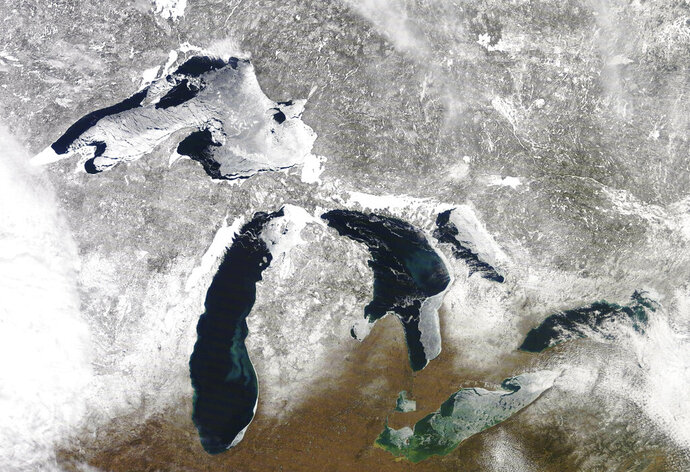 In this March 12, 2019 satellite photo provided by NOAA, shows the Great Lakes in various degrees of snow and ice. A scientific report says the Great Lakes region is warming faster than the rest of the U.S., which likely will bring more flooding and other extreme weather events such as heat waves and drought. The warming climate also could mean less overall snowfall even as lake-effect snowstorms get bigger. The report by researchers from universities primarily from the Midwest says agriculture could be hit especially hard, with later spring planting and summer dry spells. (NOAA via AP)