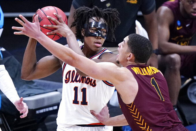 Illinois' Ayo Dosunmu (11) is defended by Loyola of Chicago's Lucas Williamson (1) during the first half of a college basketball game in the second round of the NCAA tournament at Bankers Life Fieldhouse in Indianapolis Sunday, March 21, 2021. (AP Photo/Mark Humphrey)