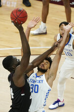 Mississippi State forward Abdul Ado (24) leans on Kentucky forward Olivier Sarr (30) as he attempts to shoot during the first half of an NCAA college basketball game in Starkville, Miss., Saturday, Jan. 2, 2021. (AP Photo/Rogelio V. Solis)