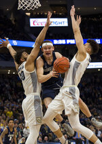 Georgetown guard Mac McClung, center, is defended by Marquette forward Ed Morrow, left, and forward Brendan Bailey, right, during the second half of an NCAA college basketball game Saturday, March 9, 2019, in Milwaukee. Georgetown beat Marquette 86-84. (AP Photo/Darren Hauck)