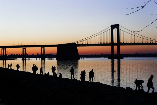 People gather to watch the sun set behind the Throgs Neck Bridge at LIttle Bay Park Wednesday, April 8, 2020, in the Queens borough of New York. While New York Gov. Andrew Cuomo said New York could be reaching a