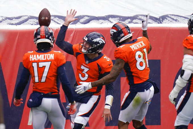 Denver Broncos quarterback Drew Lock (3) reacts with teammates wide receiver Tim Patrick (81) and wide receiver DaeSean Hamilton (17) after scoring a touchdown during the first half of an NFL football game against the Kansas City Chiefs, Sunday, Oct. 25, 2020, in Denver. (AP Photo/Jack Dempsey)