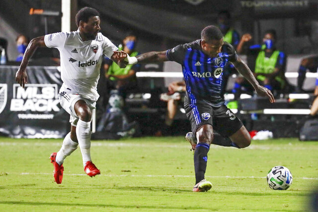 Montreal Impact forward Romell Quioto, right, tries to get off a shot in front of D.C. United defender Chris Odoi-Atsem, left, during the first half of an MLS soccer match, Tuesday, July 21, 2020, in Kissimmee, Fla. (AP Photo/John Raoux)